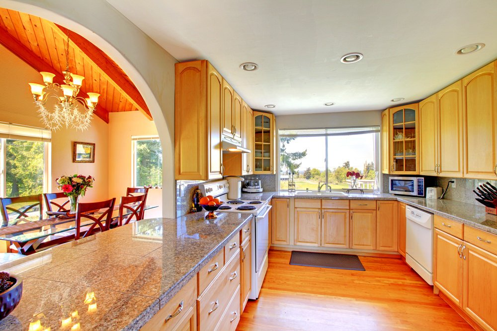 Rustic kitchen set with a classy flooring, cabinetry and counters equipped with granite countertops.
