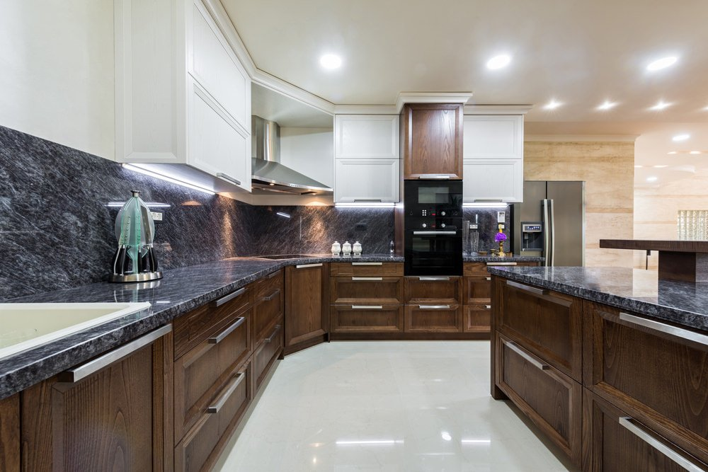 This kitchen boasts very attractive kitchen countertops and backsplash. The white tiles flooring looks perfect together with the kitchen's style.