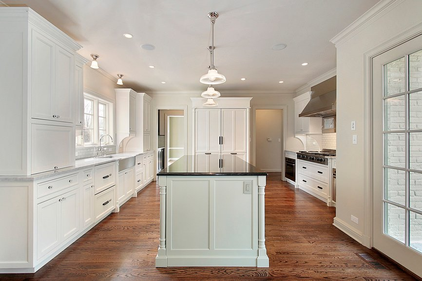 A kitchen featuring white cabinetry and kitchen counters. The white center island boasts a black marble countertop.