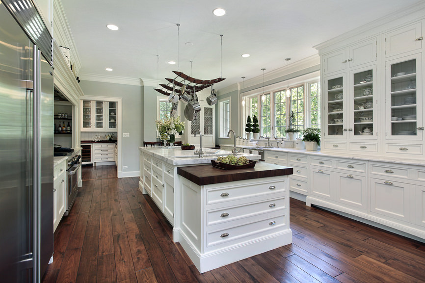 This kitchen features marble countertops on both center island and kitchen counters. The room boasts gray walls and hardwood flooring.
