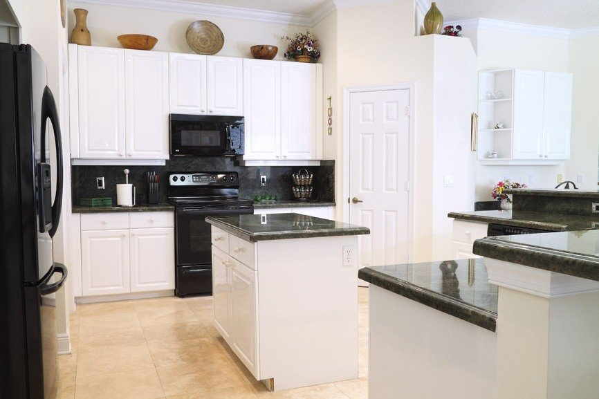 White kitchen featuring tiles flooring, black counters and appliance and a small center island and peninsula.