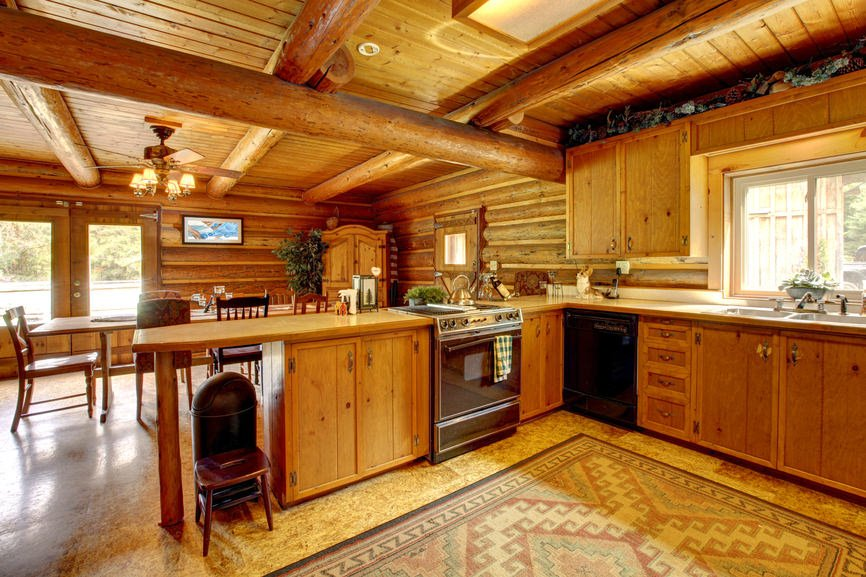 A large rustic kitchen with a jaw-dropping ceiling and walls. The flooring looks classy together with the rug on top of it.