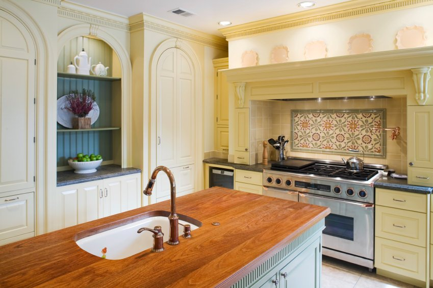 Beige kitchen with crown molding, decorative tile backsplash, and a kitchen island with wood surface, sink, and base cabinet.