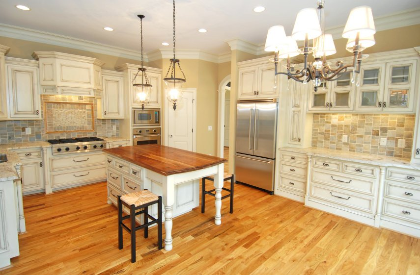 Beige kitchen with chandeliers, recessed and pendant lights, white cabinetry, stone tile backsplash, and a white base cabinet kitchen island with wood surface standing on medium-toned wood flooring.
