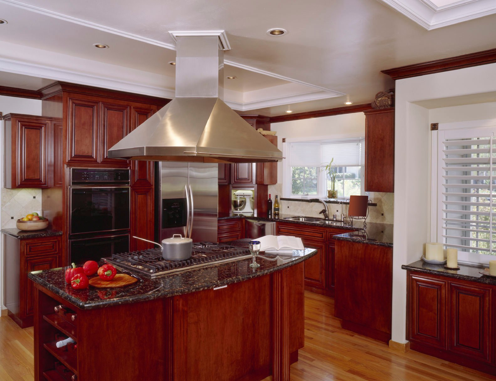 This kitchen offers reddish kitchen counters and center island with granite countertops. The tray ceiling adds style to this kitchen.