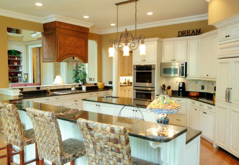 This kitchen lighted by classy pendant and recessed lights also features a center island and a peninsula.