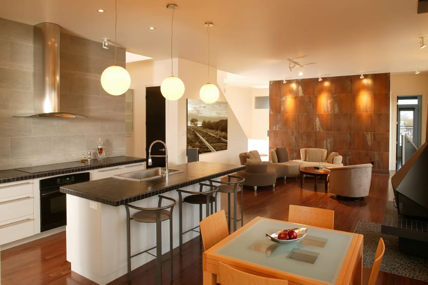 This industrial kitchen offers a breakfast bar and a dining nook, lighted by pendant and recessed lights.