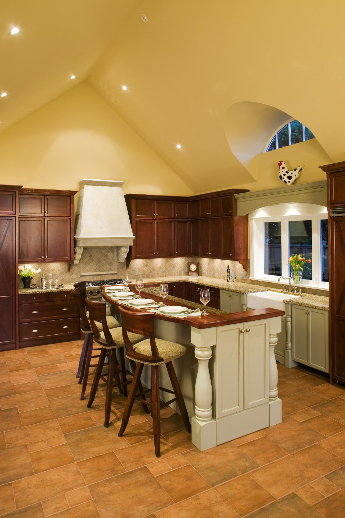 This kitchen boasts beige walls and tiles flooring, along with a stylish center island that provides space for a breakfast bar.