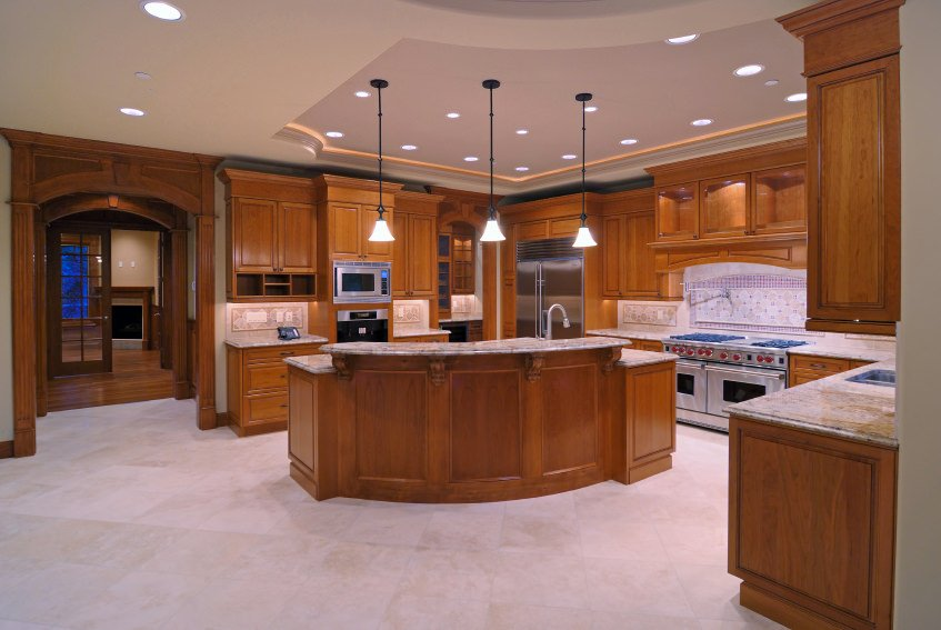 Large kitchen featuring walnut finished cabinetry, kitchen counters and center island, both with marble countertops. The pendant and recessed lights are set on the beautiful tray ceiling.