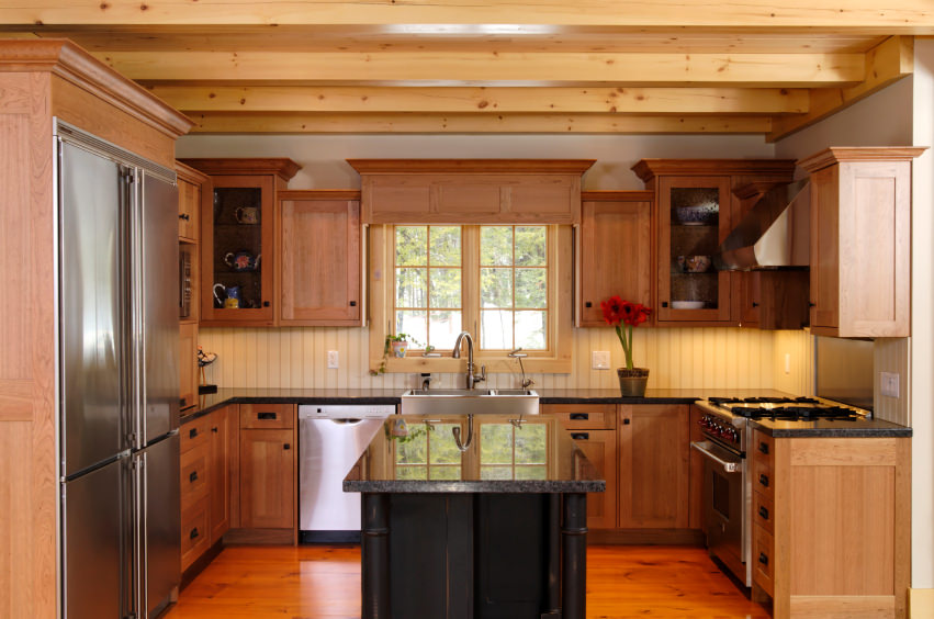 This kitchen boasts a very stylish center island with black finish and granite countertop set on the hardwood flooring. This kitchen also features a ceiling with beams.