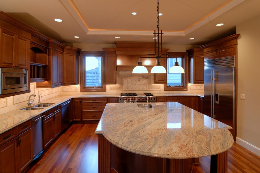 This kitchen offers marble countertops on both kitchen counters and center island. The lighting set on the tray ceiling looks stunning as well.