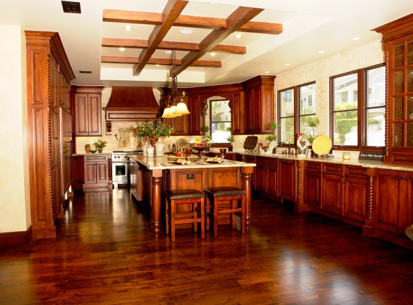 This glamorous kitchen boasts reddish hardwood floors matching the cabinetry and kitchen counters with marble countertops. The tray ceiling with beams features gorgeous pendant lights.