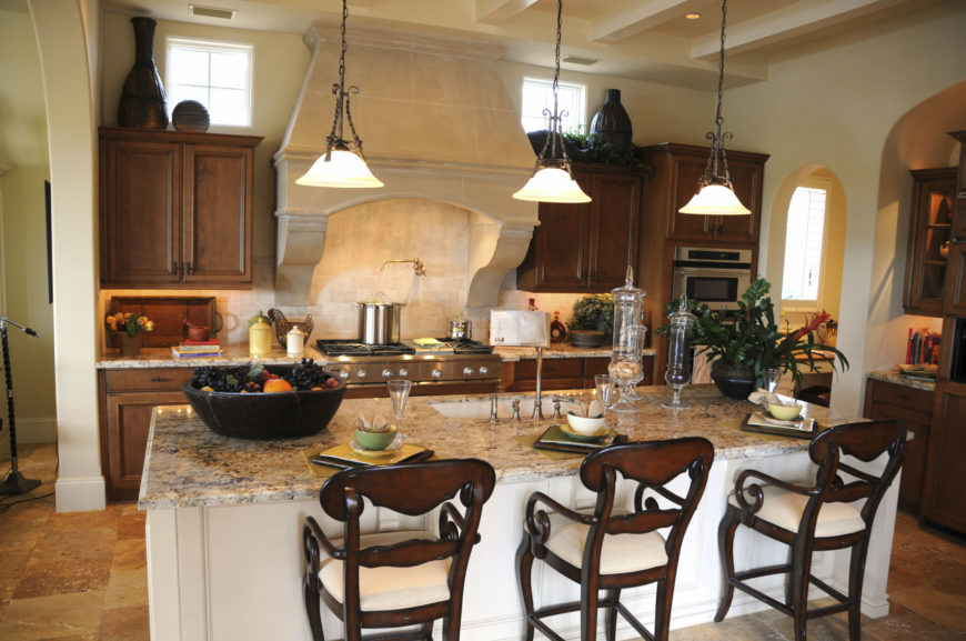 Wrought iron pendant lights illuminate this kitchen featuring white breakfast island with marble countertop and sink. It has wood cabinetry and beige range hood fixed to the brick backsplash tile.