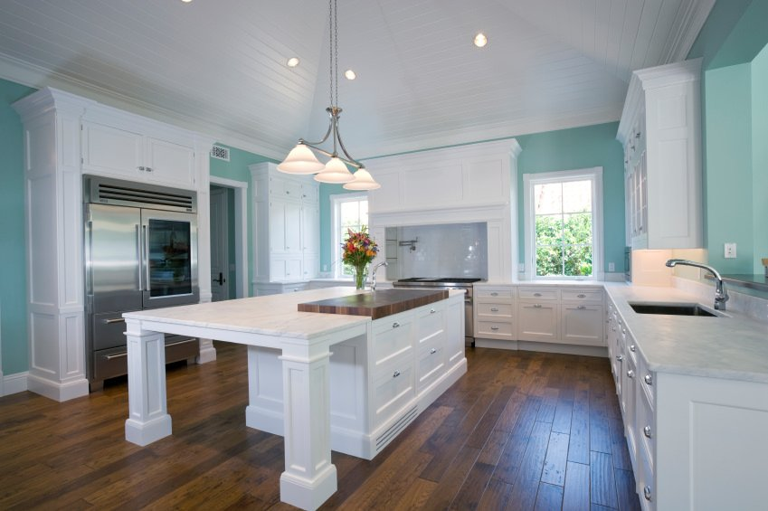 This Mediterranean kitchen boasts a mix of white, green and brown colors. It features white cabinetry, green walls and a hardwood flooring. The center island is lighted by three pendant lights.
