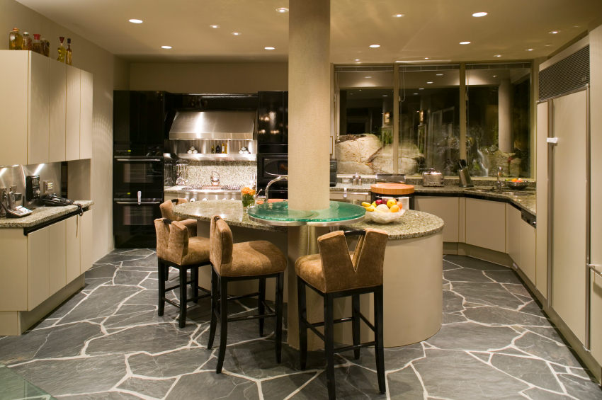 This kitchen boasts a central breakfast island attached to the white column and paired with brown velvet counter chairs over black flagstone flooring.