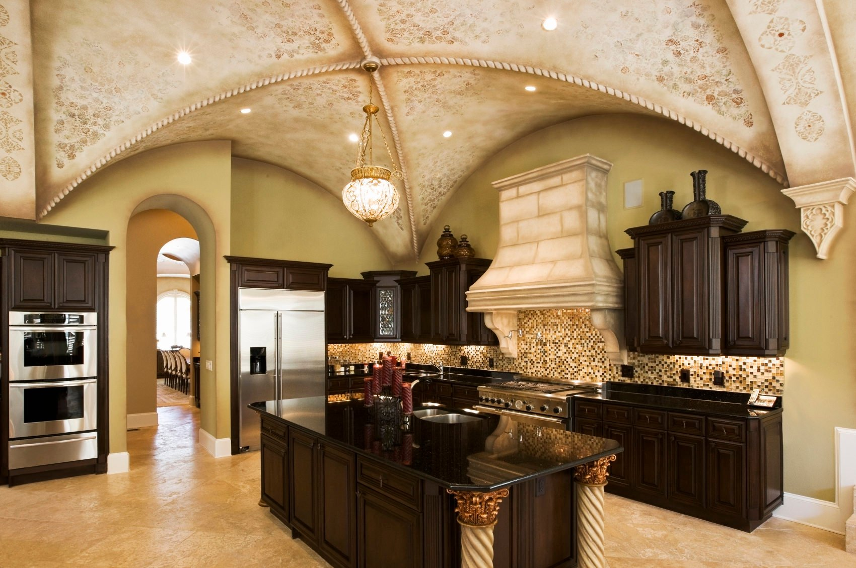 This kitchen is oozing with elegance because of its stunning groin vault ceiling. The lighting looks perfect as well, while the cabinetry, counters and center island with dark countertops look absolutely beautiful.