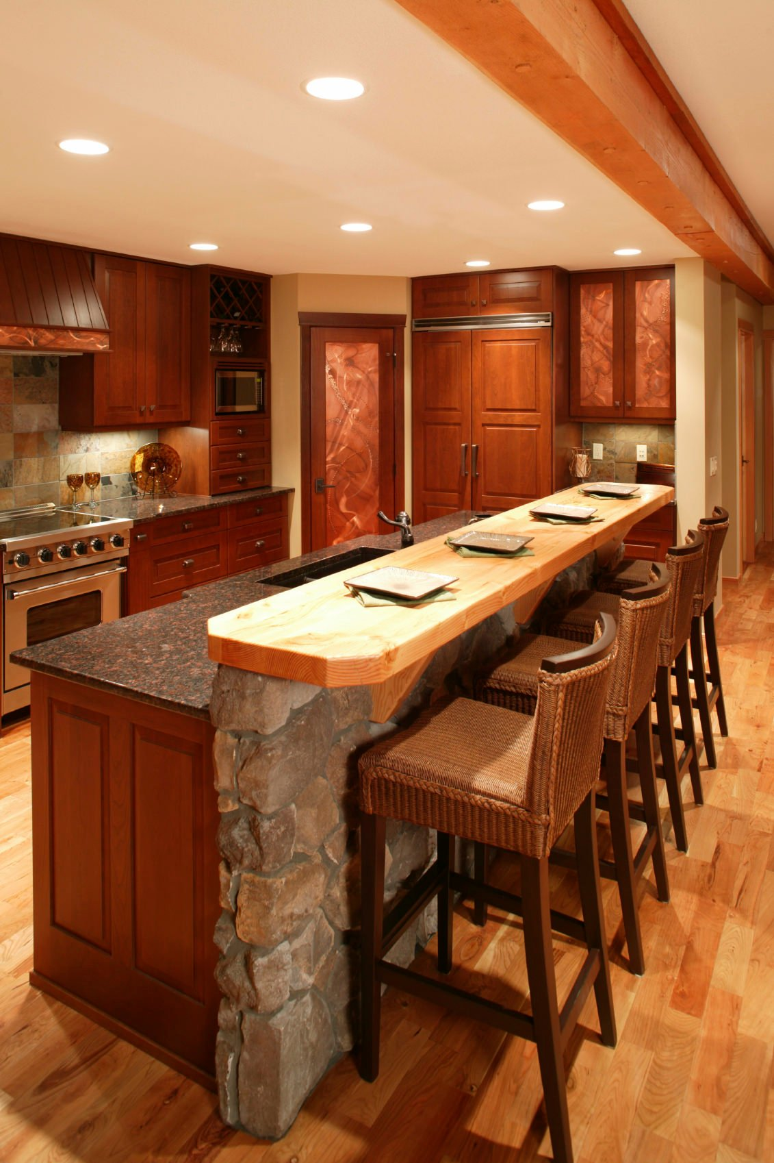 Rustic kitchen with red-toned wood cabinetry and a two-tiered bar-style kitchen with a stone base for the upper tier with wood surface.