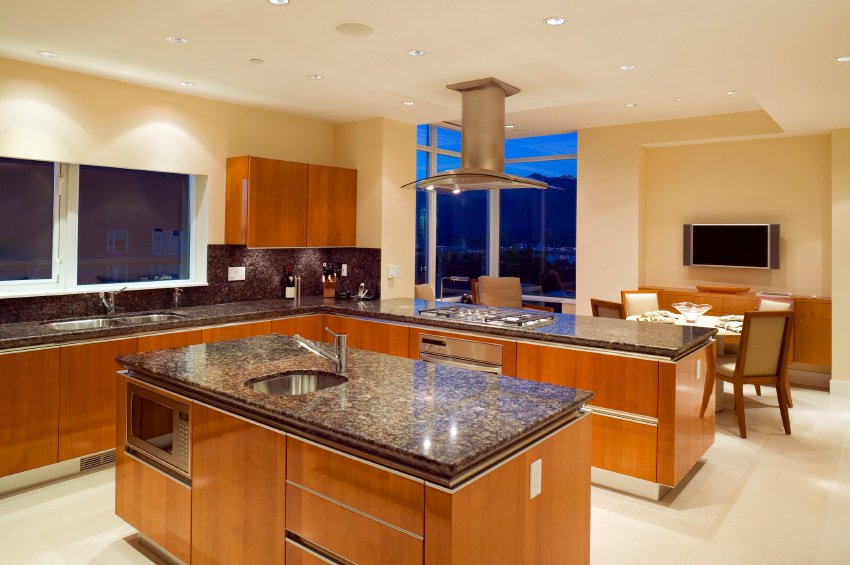 This kitchen features granite countertops matching well with the walnut cabinetry. The recessed lights add classy vibe to the room's style.