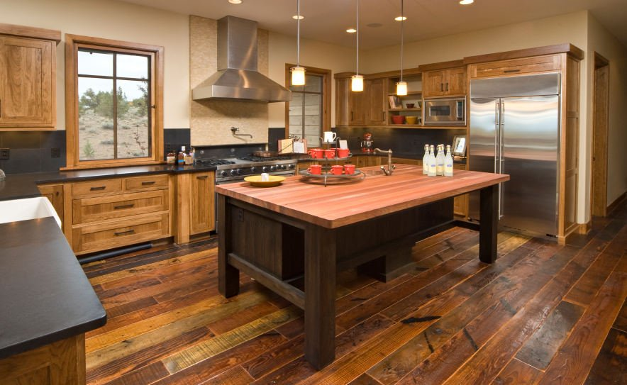 Rustic kitchen set with a hardwood flooring and a large center island with a plank countertop lighted by pendant lights.
