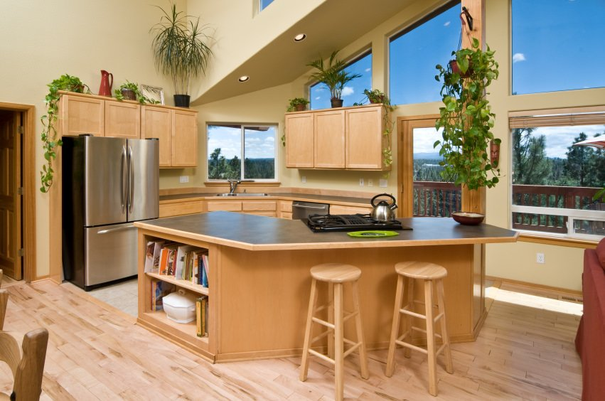 A kitchen featuring walnut-finished cabinetry and kitchen counters along with a massive center island set on the hardwood flooring.