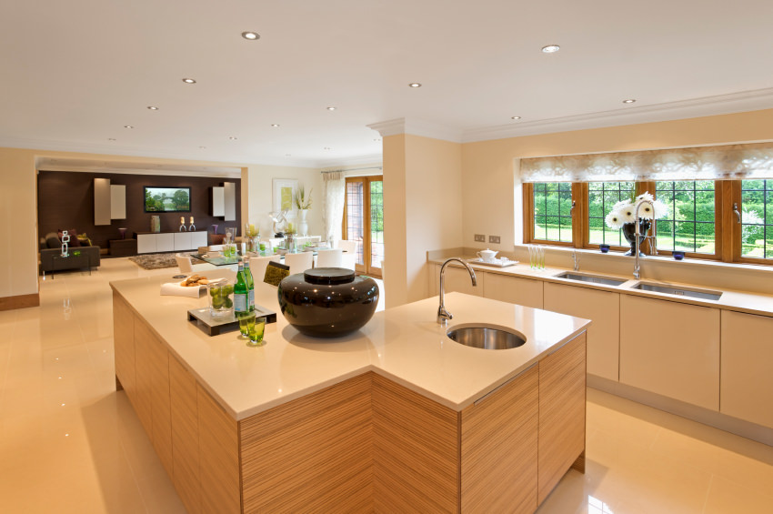 This kitchen boasts a light wood breakfast island topped with a white marble counter that matches the tiled flooring. It has white cabinetry with beige countertop and dual sink.