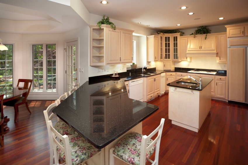 This kitchen boasts a reddish hardwood flooring and black granite counters spreading across the kitchen. There's a small center island and a peninsula.