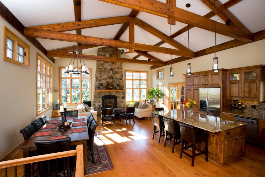 Large great room featuring a large center island providing space for a breakfast bar, a living space with a fireplace, and a dining table set for eight, all under the stunning vaulted ceiling with exposed beams.