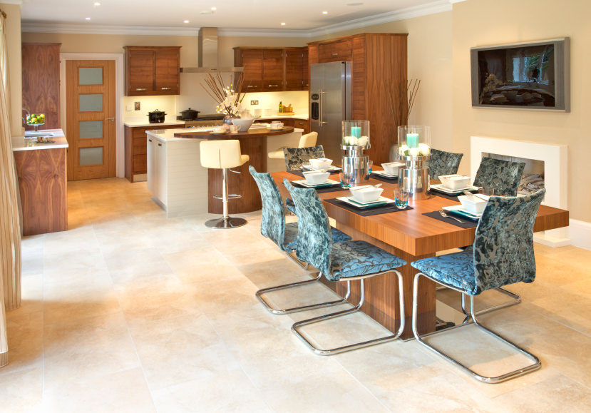 This kitchen offers a modern dining table set with a stunning table and stylish chairs, along with a fabulous looking breakfast bar.