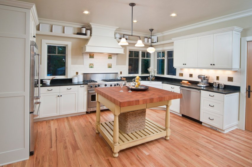 White kitchen with black countertop, recessed and pendant lights, and a small wood table island on a light wood flooring.