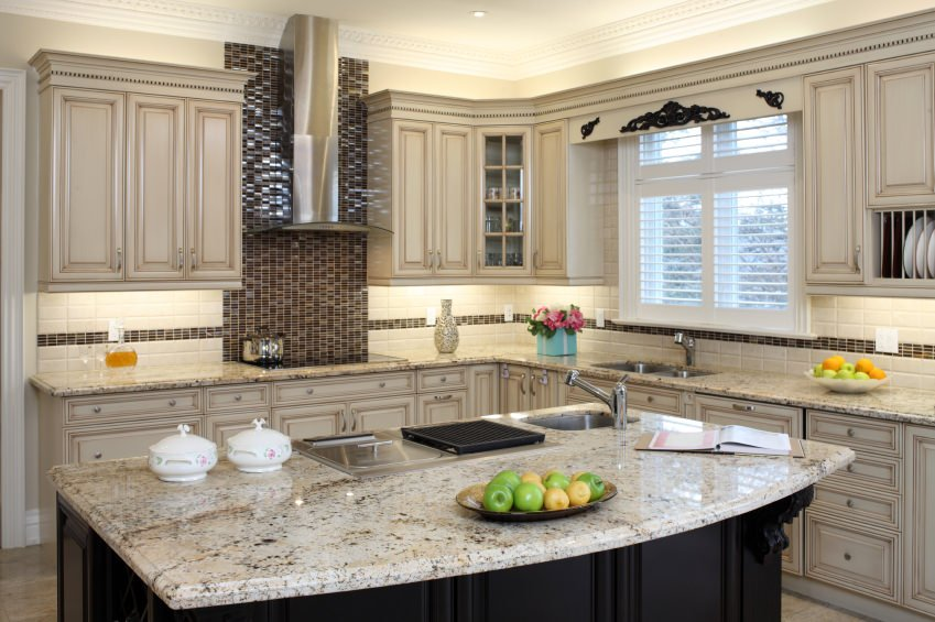A close up look at this kitchen's breakfast bar with a beautiful countertop. The cabinetry and kitchen counters are both classy.
