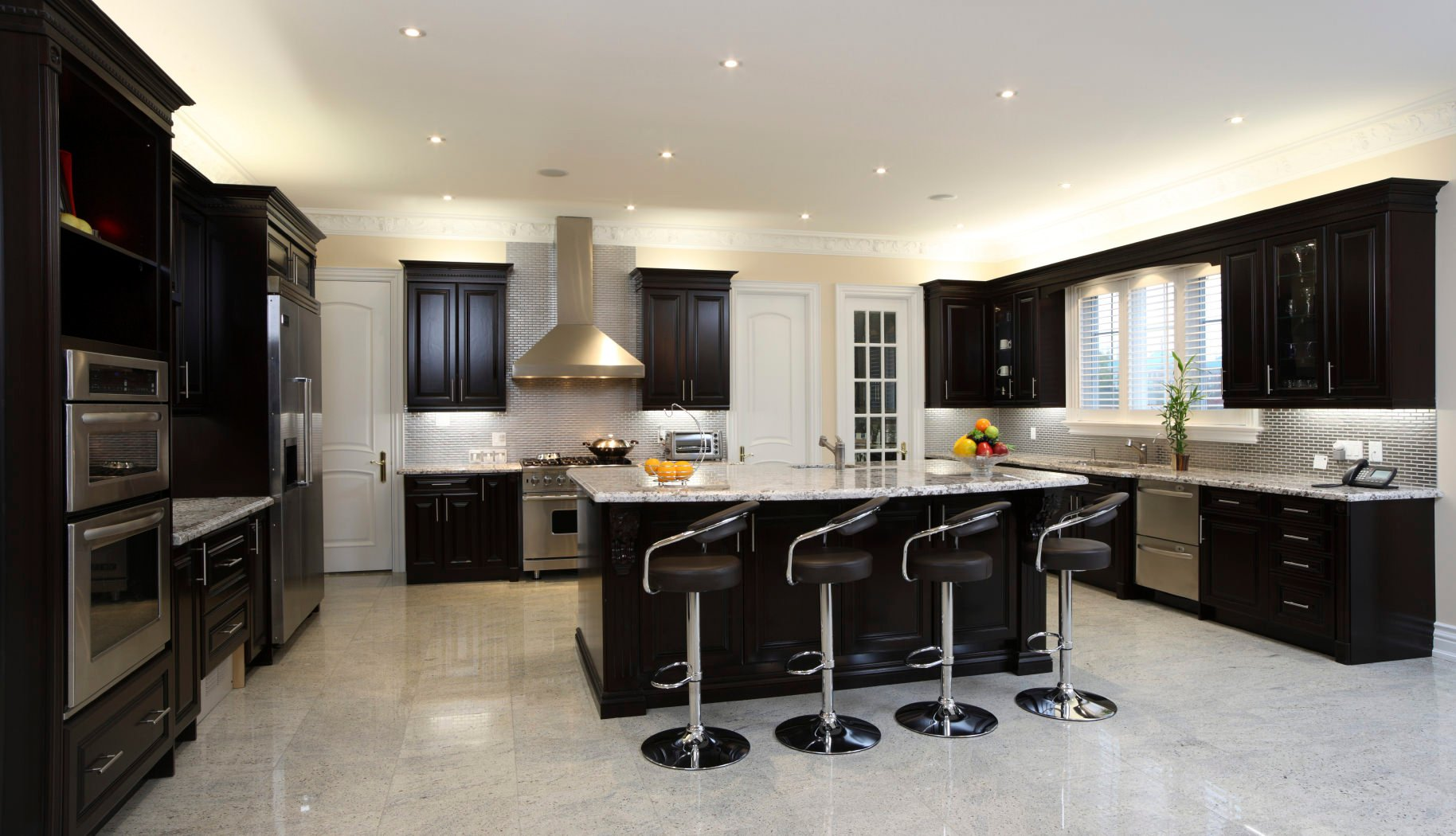 Black and white themed U-kitchen with black enamel cabinets, stainless steel appliances, breakfast island, and tiled floor.