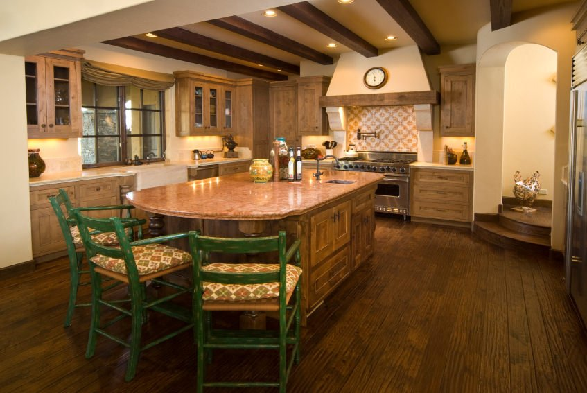 Large kitchen with rustic cabinetry, kitchen counters and a massive center island with a classy countertop and breakfast bar stools, lighted by recessed lights set on the ceiling with beams.