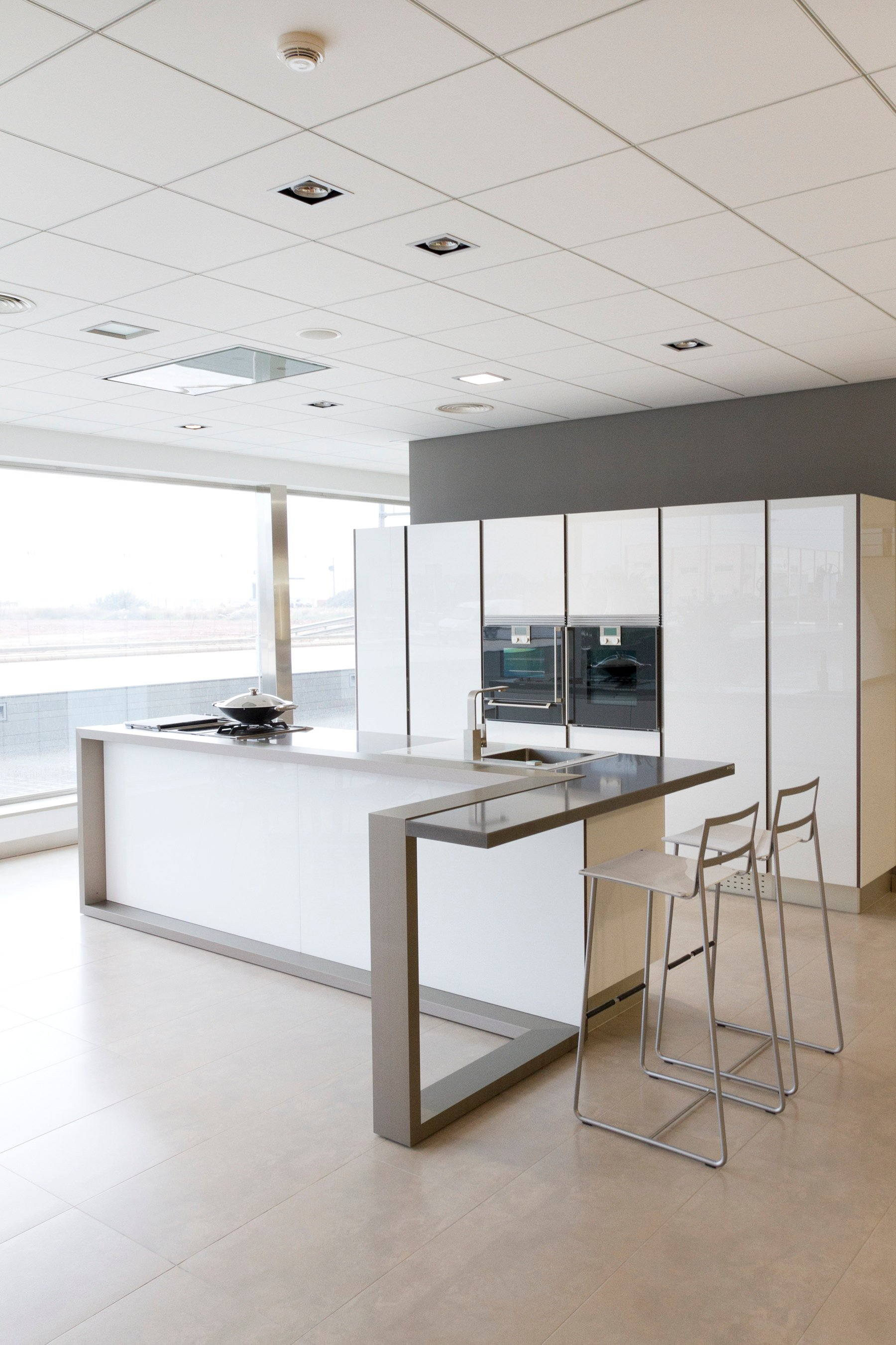Here's a compact white kitchen with l-shaped small island in a modern style.