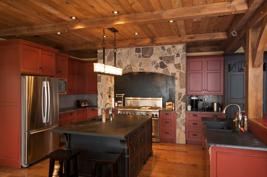 This kitchen boasts an elegant black center island, pairing with the red cabinetry and kitchen counters. The ceiling lights are absolutely gorgeous, along with the wooden ceiling with beams.