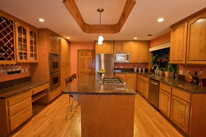 This kitchen is surrounded by walnut finished cabinetry, kitchen counters and center island, both with granite countertops. The warm white lights set on the tray ceiling look so lovely.