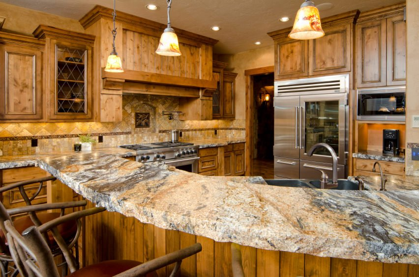 This rustic kitchen features a very stylish breakfast bar countertop lighted by glamorous pendant lights.