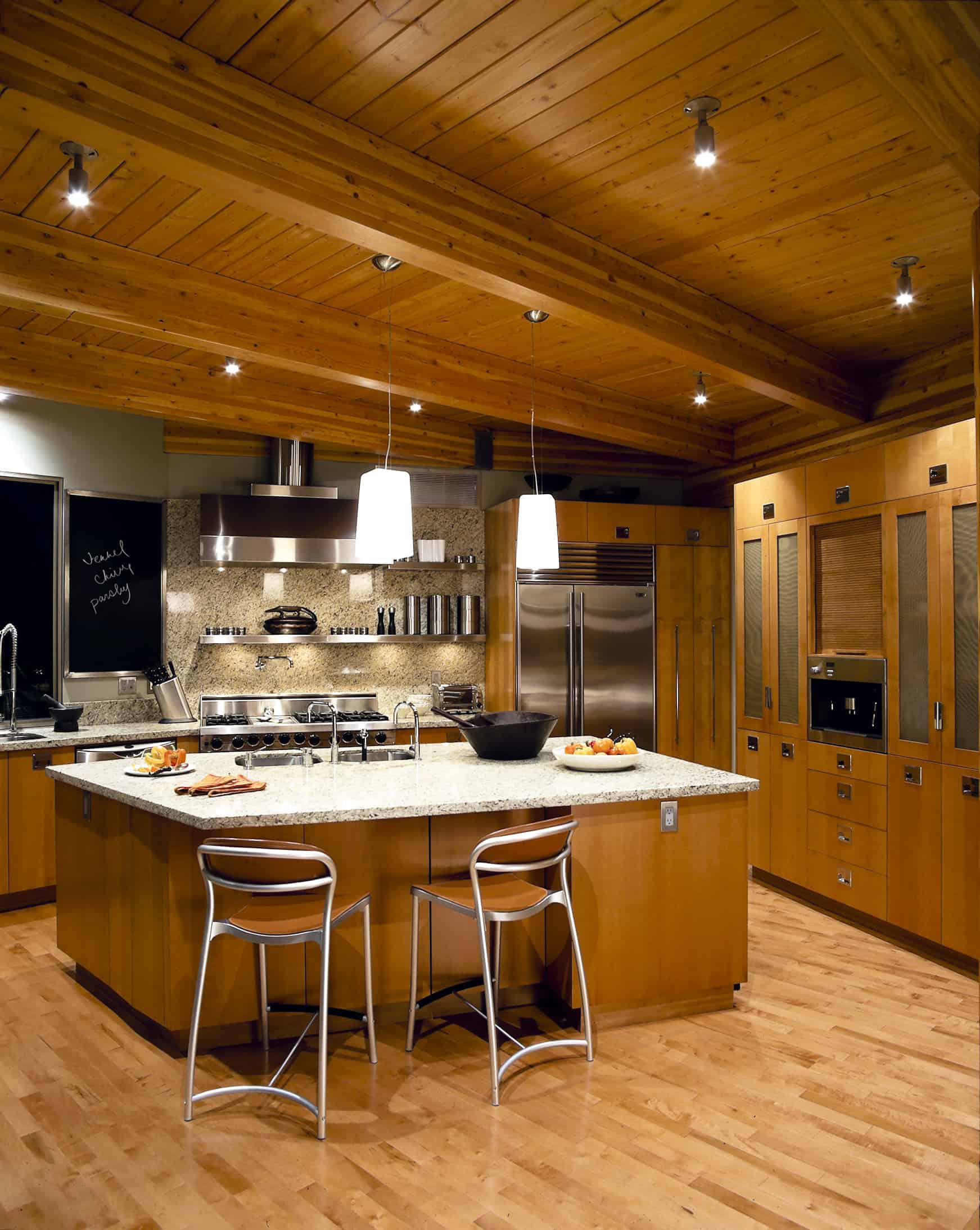 This kitchen boasts a large center island with beautiful marble countertop set on the hardwood flooring that matches the wooden ceiling with exposed beams.