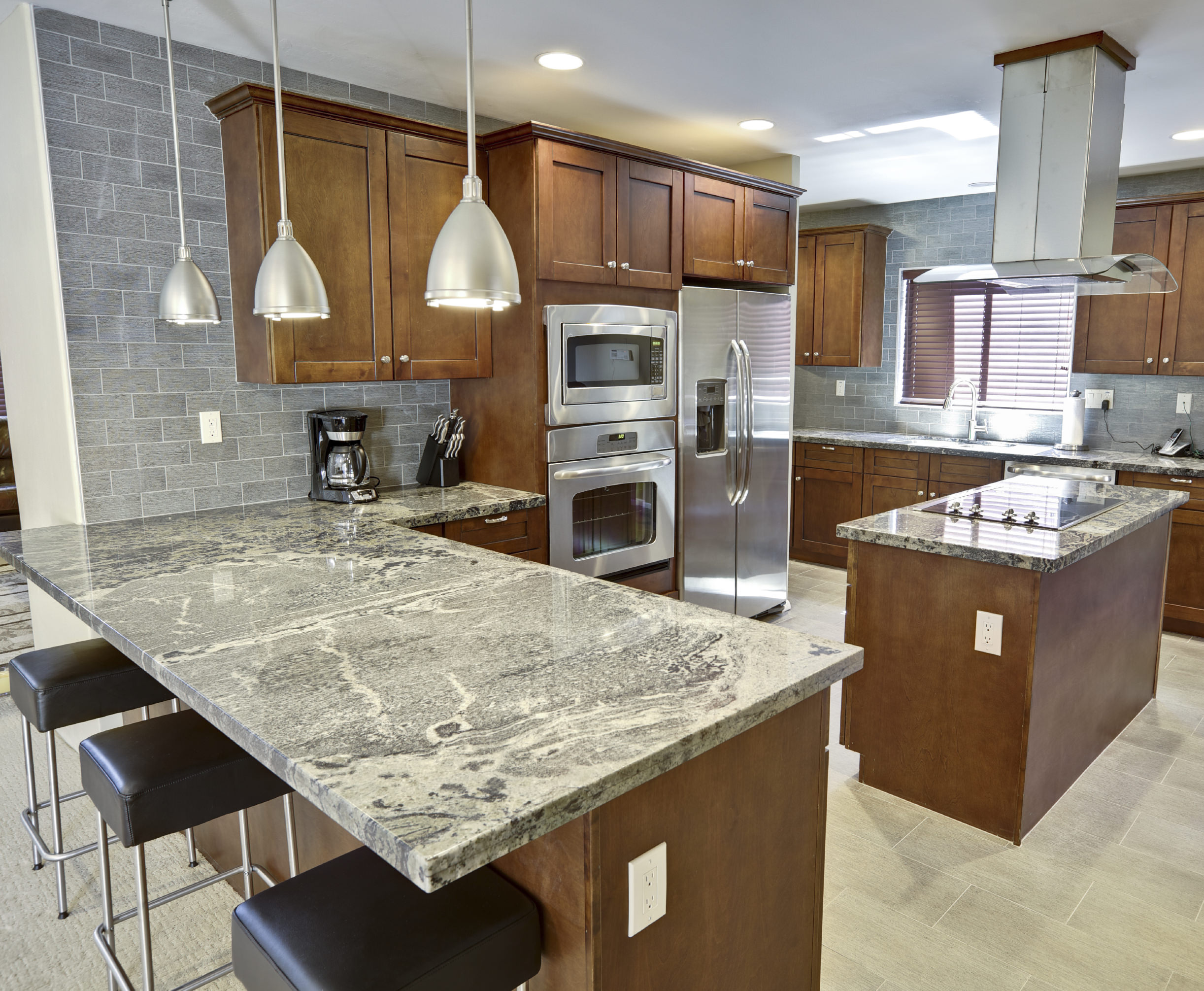 Kitchen with a breakfast bar featuring stylish kitchen and island countertop. A ceiling lighted by recessed and pendant lights, along with gray tiles walls.