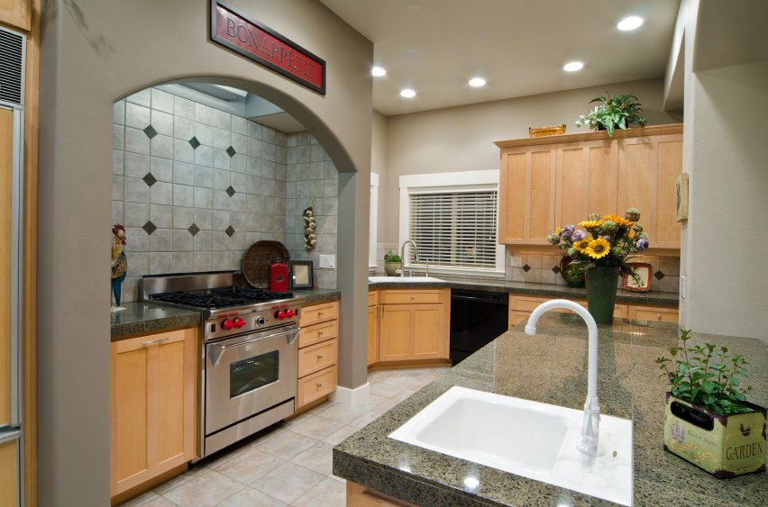 A kitchen featuring a center island and kitchen counters with granite countertops surrounded by gray walls. The cabinetry is finished with walnut.