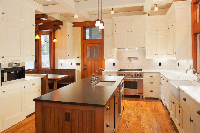 This kitchen boasts white cabinetry, backsplash and counters, along with a center island with black countertop set on the hardwood flooring. The ceiling with beams look absolutely lovely.