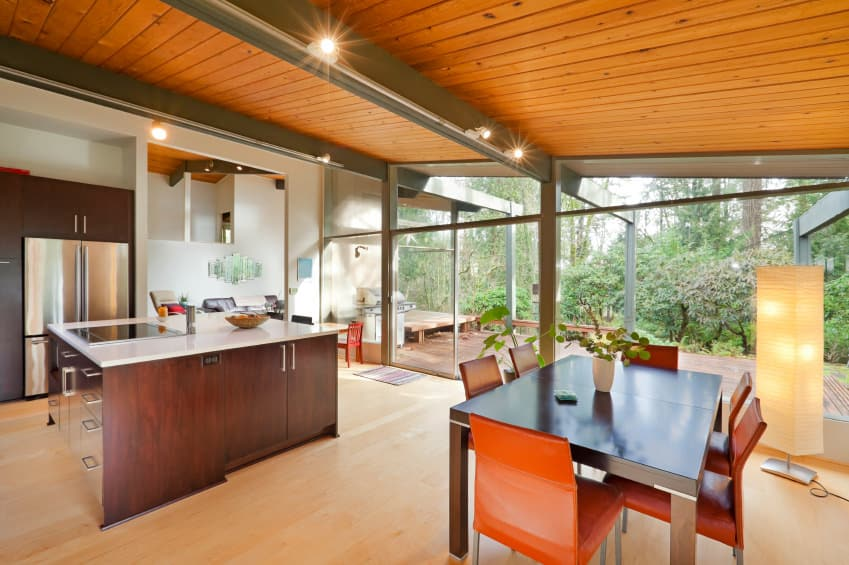 This kitchen offers a beautiful center island and a small dining table set, lighted by track lights installed on the ceiling's beams.