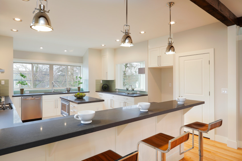 White kitchen featuring dark smooth counters spreading across the kitchen. There's a center island and a peninsula lighted by recessed and pendant lights.