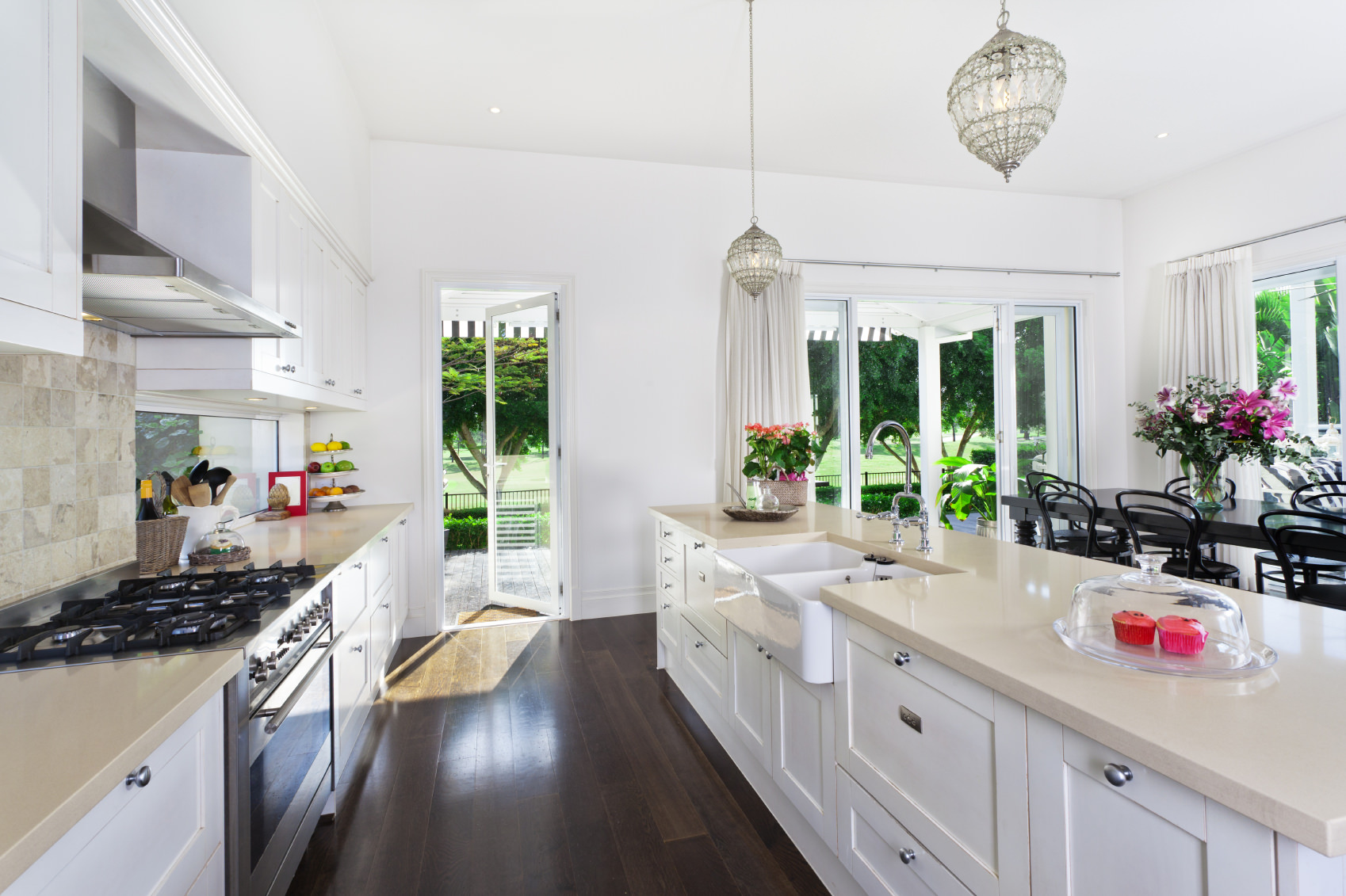 White Mediterranean kitchen with dark hardwood flooring. The beautiful greenery outside can be overlooked through the doors and windows. The center island is long and has a smooth white countertop.