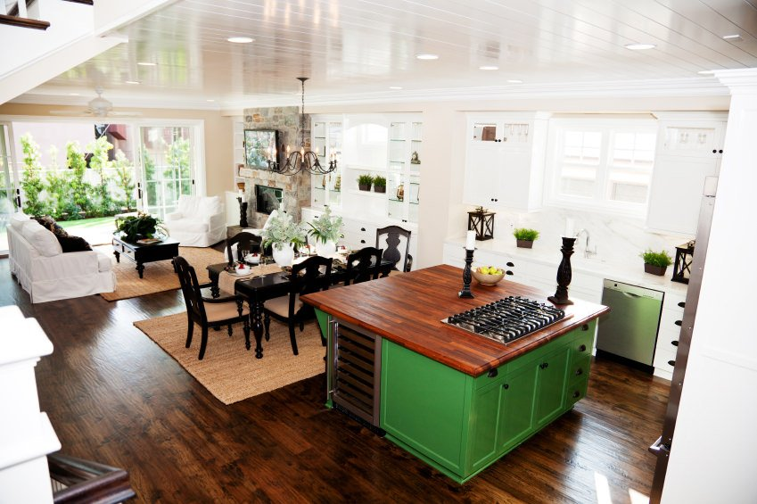 Small kitchen with white cabinetry, wood flooring, and a green kitchen island with base cabinets, dishwasher, cooktop, and a wood surface.