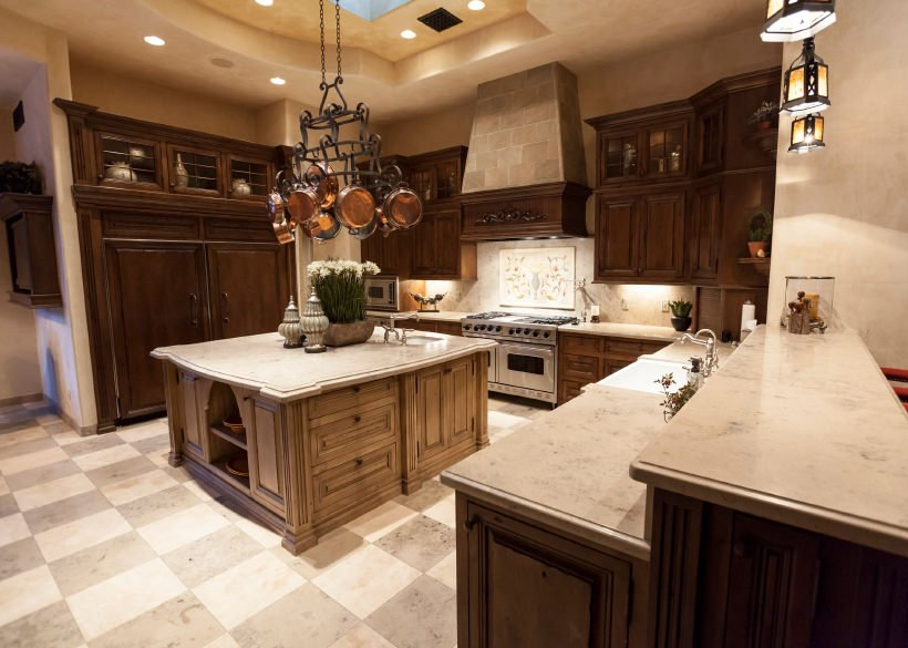 This kitchen features a checker flooring, smooth marble counters spreading across the kitchen and elegant sets of recessed and pendant lights.