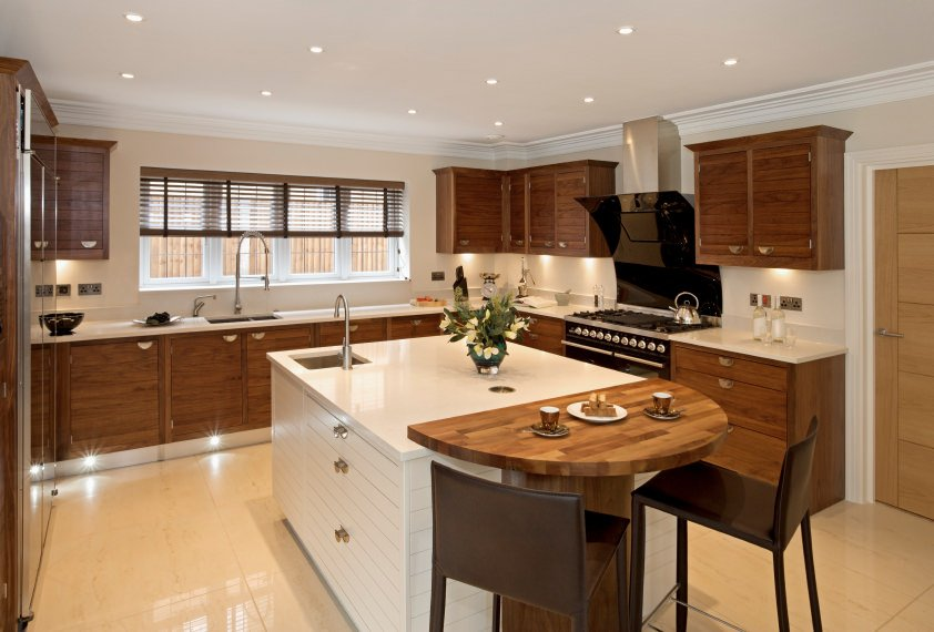 Kitchen with shutter windows by the sink, flat panel cabinets, black cooking range and hood, and a double-tiered white base cabinet island with wood surface for the breakfast counter.