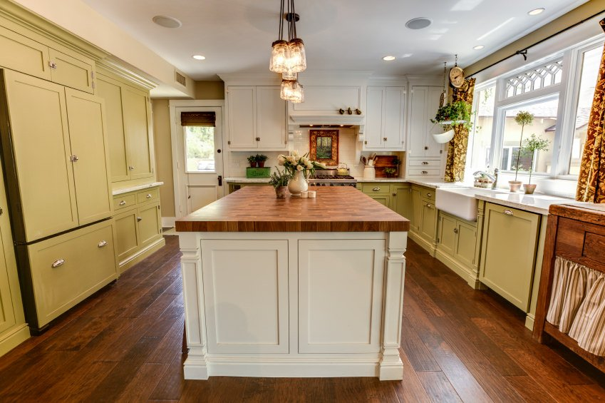 Kitchen with some white upper cabinets and a Farmhouse sink by the window surrounded by olive green cabinets and pendant lights on a massive white kitchen island with wood surface.