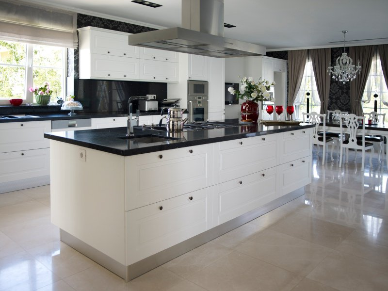 This kitchen boasts a large center island with black countertop matching the kitchen counters' countertop.