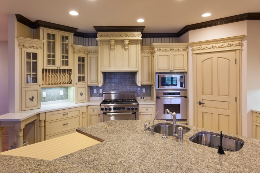 A kitchen with classy cabinetry and a semi-circular center island with a stylish countertop lighted by recessed lights.