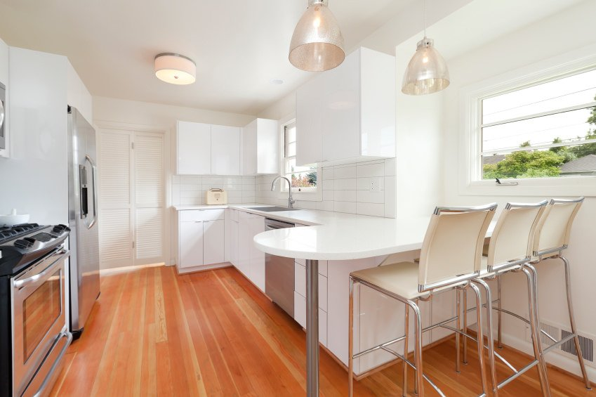 A Scandinavian-Style kitchen featuring a reddish hardwood flooring, which matches well with the white walls, counters, cabinetry and the breakfast bar on the corner.